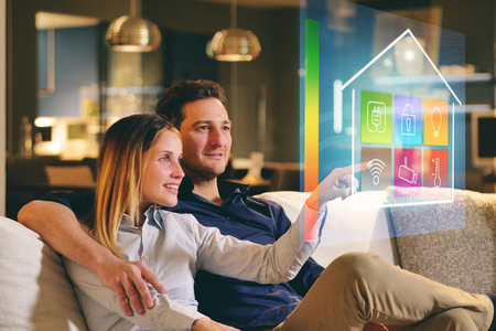 A couple sitting on the sofa controls all the functions of the house such as wifi, heating, lighting, and television through holography. Concept of, home automation, automations, future, technology. Stock Photo