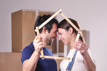 Just love a house and is moving. The bride and groom smile and hold the house. Concept of: future, family, mortgage and loan. Reklamní fotografie