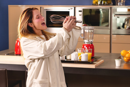 Hand in mix to eat woman in kitchen in pajamas singing holding a ladle. The woman enjoys singing to the rhythm of music. Concept of: music, happiness, song and home.