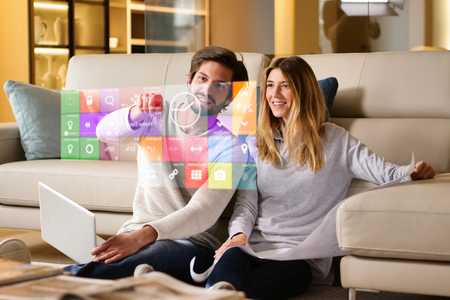 A couple sitting on the sofa controls all the functions of the house such as wi-fi, heating, lighting, and television through holography. Concept of, home automation, automations, future, technology.
