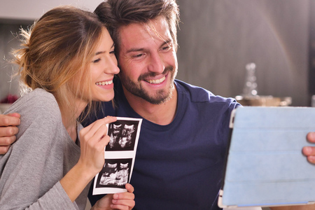 A couple in love videocall their parents using a tablet, to announce the birth of their son showing the ultrasound. Concept of: family, birth, life, love