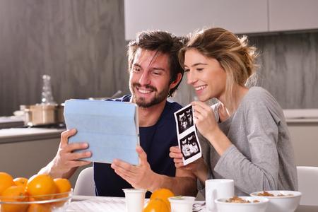 Un couple amoureux appelle en vidéo ses parents à l'aide d'une tablette, pour leur annoncer la naissance de leur fils en montrant l'échographie. Concept de : famille, naissance, vie, amour