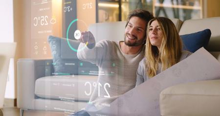 Una coppia seduta sul divano controlla tutte le funzioni della casa come wi-fi, riscaldamento, illuminazione e televisione attraverso l'olografia. Concetto di, domotica, automazioni, futuro, tecnologia.