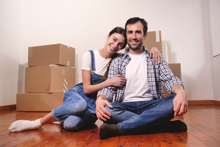 A loving couple who are buying the new house and moving away. The couple are smiling and happy with the futuristic project together. Concept of: future, family, design and projects.
