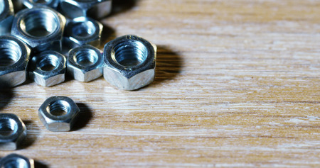 bolts and screws on a wooden work bench. concept of new screws or bolts. working tools in carpentry and home. and self-tapping steel screws