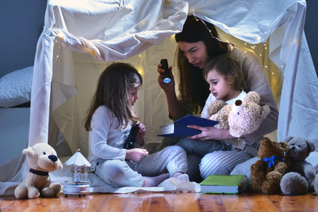 A mother with her daughters plays in the bedroom to read fairy tales in a tent built with sheets. Concept of: family, protection, educational, magic, creativity. Stock Photo