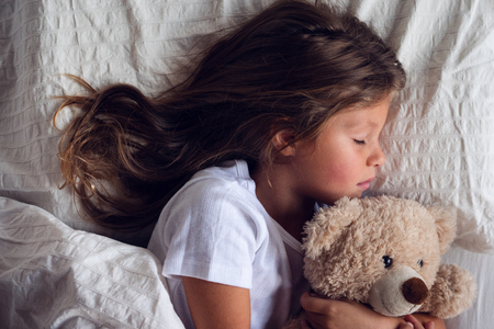 A beautiful girl sleeps and has her dreams. The girl smiles because she is relaxed and sleeps well. Concept of: relax, love sleep. Banque d'images