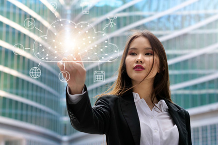 A businesswoman looks in front of him at the cloud archiving icon that appears with futuristic graphics. Concept of: connection, cyber-security, holography, future ...