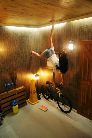 Una mujer está en un mundo donde todo es al revés. La niña está en un dormitorio pequeño pero los muebles cuelgan del techo.