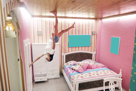 A woman is in a world where everything is the opposite. The girl is in a small bedroom but the furniture is hanging from the ceiling.