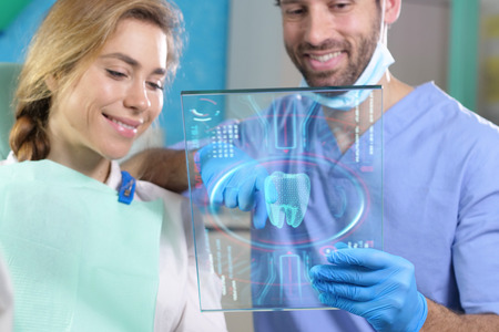 In a professional practice, a dentist checks the patient's denture plate, and she smiles happily, showing her perfect smile. Concept of: future, technology, dentists, healthcare. Stock Photo