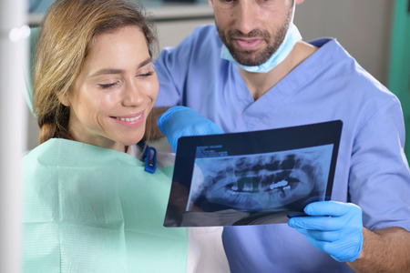 In a professional practice, a dentist checks the patient's denture plate, and she smiles happily, showing her perfect smile. Concept of: dentists, healthcare, medical examination.