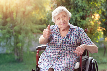 Portrait of an elderly lady sitting on the wheelchair smiling happily and making