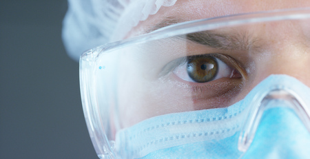 A doctor or surgeon in a medical mask, a respirator, brown eyes, goggles, a surgical cap, a hospital or clinic.