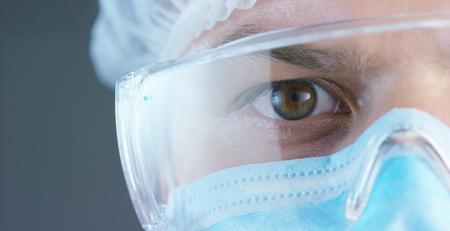 Ein Arzt oder Chirurg in einer medizinischen Maske, einem Beatmungsgerät, braunen Augen, einer Schutzbrille, einer chirurgischen Kappe, einem Krankenhaus oder einer Klinik. Standard-Bild