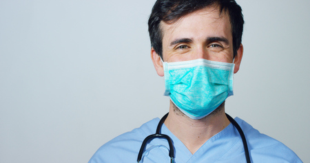 close up portrait of a surgeon or doctor with mask ready for operation in hospital or clinic. Stock Photo