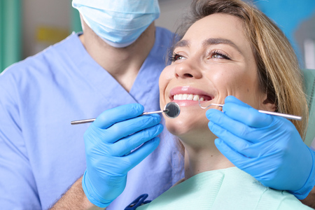 In a professional practice, a dentist checks the dentition of the patient, and shows the perfect white teeth. Concept of: dentists, healthcare, perfect smile.
