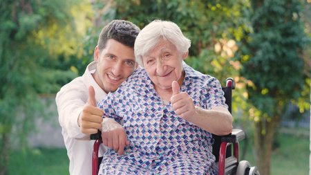caring for the elderly, boy (man), hugging grandmother, smiling, happy, walking in the park. Concept: boarding house, sanatorium, a house for the elderly, help for the elderly.