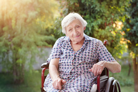 Portrait of an elderly lady sitting on the wheelchair smiling happily and making ok with her hand. The elderly person in the nursing home. Imagens