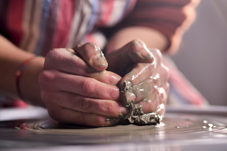 An expert potter, he creates with clay and his hands in a beautiful vase in his laboratory. The artisan creates works of art with his hands. Concept of: experience, art, tradition, clay. Stockfoto