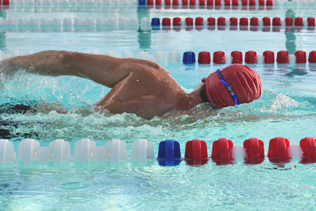 A professional swimmer trains with a pool and a freestyle pool. Concept of: sport, swimming pool, competition, fitness.