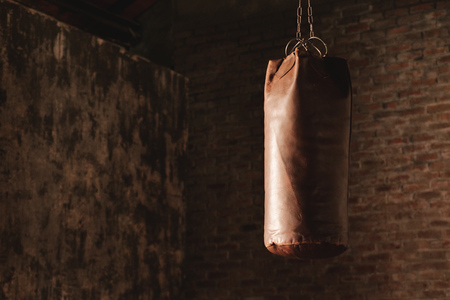 Still life of a boxing bag with a chain, in an urban gym with exposed bricks. Concept of: sports, athletes, boxing, passion, tradition, power 版權商用圖片 - 113649481