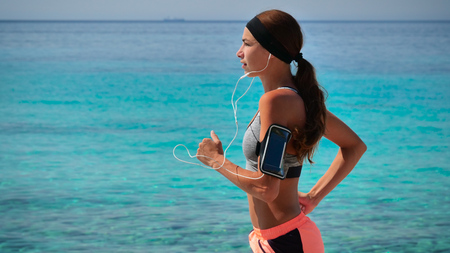A professional runner confidently runs into sportswear listening to music on the phone.