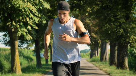 Portrait of a handsome young guy in sportsman, holding a phone, smiling, wearing sports clothes, running outside. Concept: love sports, healthy lifestyle, beautiful, muscles, happy, burn calories.
