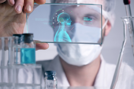 A futuristic physician, a surgeon, examines a technological digital holographic plate, a medical mask, a cap, brown eyes. Concept: futuristic medicine, new technologies, doctors, laboratory, future.