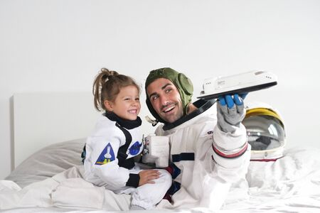Romantic and family moments of dad and daughter playing with spacecraft, both dressed as astronauts and are happy at this unique moment. Concept of: love, family, home, games.