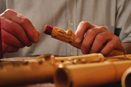 A flute maker builds sweet flutes and crosspieces, made exclusively by hand and precious wood or ivory, in his own laboratory. Concept of: music, craftsmanship, tradition