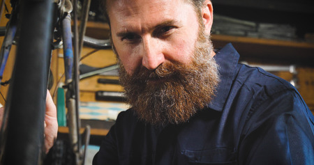 Well-groomed handsome bearded master hipster, specialist in bicycles, repairing a bicycle in his workshop, wheels, frames, spokes, the background of tools. Concept: pro bike, cycle passion, lifestyle.