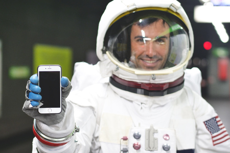 An astronaut dressed in the smartphone to call and send messages. The astronaut smiles while looking at the phone in his hand. Concept of: Phone Promotions, Messages and Spatial Calls.