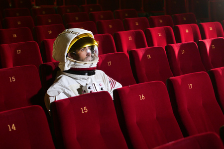 Astronaut looks at a movie while eating popcorn and enjoying the movie. Concept of: cinema and space films, film of the other world, surreal situations.