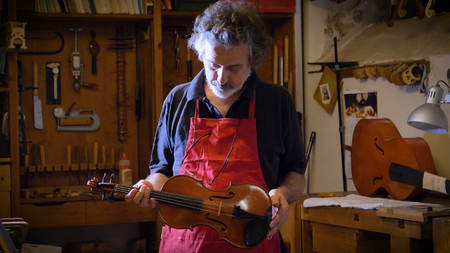 The professional violin master makes a violin with his own hands, spruce, pine, glasses, planes, tunes strings. Concept: spiritual instrument, made hands, art, music, melody, sound