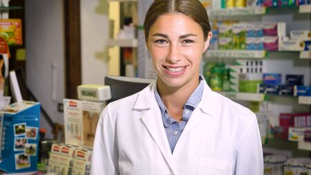 Portrait of a beautiful young girl (woman) pharmacist, consultant, working at a pharmacy, smiling and giving medication. Concept: profession, medicine, medical education.