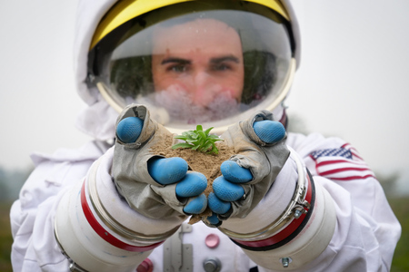 An astronaut lands on a planet. He takes a sprout and hears it carefully. Concept of: ecological, new worlds and new life, exploration and science Banco de Imagens