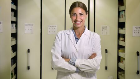 Portrait of a beautiful young girl (woman) pharmacist, consultant, working at a pharmacy, smiling and giving medication. Concept: profession, medecine, medical education. Banco de Imagens