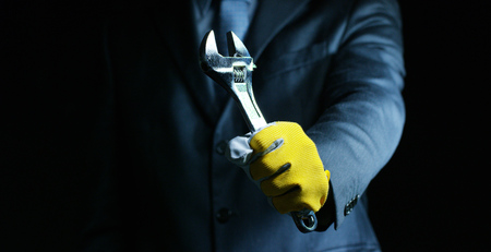 A man dressed in a suit and tie, showing a wrench mechanic. Concept: car insurance, mechanical, leasing