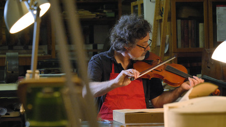 The professional viola master plays the violin with his own hands, uses a pure spruce tree, pine, in the workshop. Concept: spiritual instrument, hand made, art, music, melody, sound, musician. Stock Photo