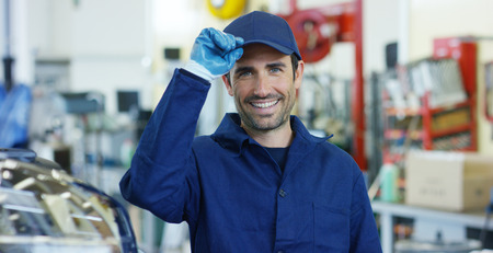 Portrait of a young woman in a car workshop, in the background of a car service.