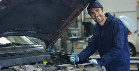 Auto mechanic specialists in car service, checks the car, engine, engine, carburetor. Concept: repair of machines, fault diagnosis, repair specialist, technical maintenance and on-board computer.