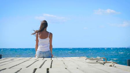 A woman sitting on a wooden pier looking at the sea. Concept: freedom, beautiful sea view, happy people, vacation, beautiful portrait. Stock Photo