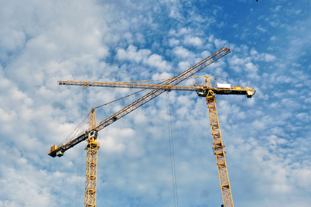 two crane of construction site, while they are working. Concept: work, labor, construction Banco de Imagens - 118557900