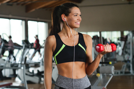 While looking at the gym, a beautiful girl, smiles and listens to the music.