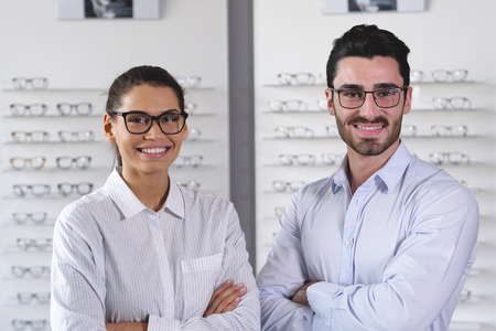 A vision of a pair of ophthalmologists, who makes eye-ophthalmological for a client in an optical center. Try the spectacles to the patient. Concept of: medical examination, assistance, optics Archivio Fotografico