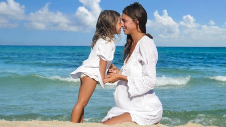 A pregnant mother and her daughter are happily playing at the sea. Archivio Fotografico