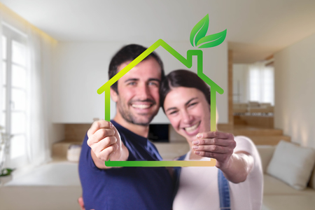 Just love a house and is moving. The bride and groom smile and hold the outline of a house. Concept of: home, family, ecology