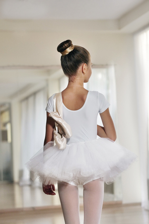 A beautiful girl in a dance school, wearing a white tutu, and holding her shoes. Concept of: ambition, education, elegance and love for the dance