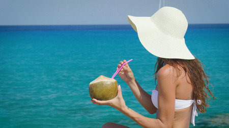 Beautiful young girl drinks a coconut cocktail by the sea, in a white bikini, sunglasses, golden sand background. Concept: sea vacation, freedom, sun, travel, waves, fresh fruit, vacation, diet, hot.